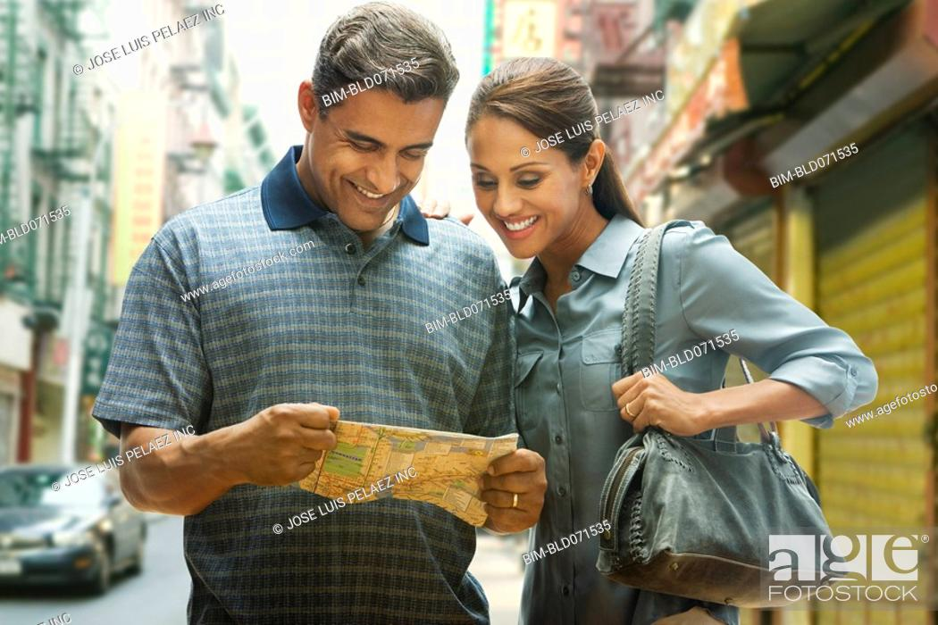 Stock Photo: Hispanic couple looking at street map.