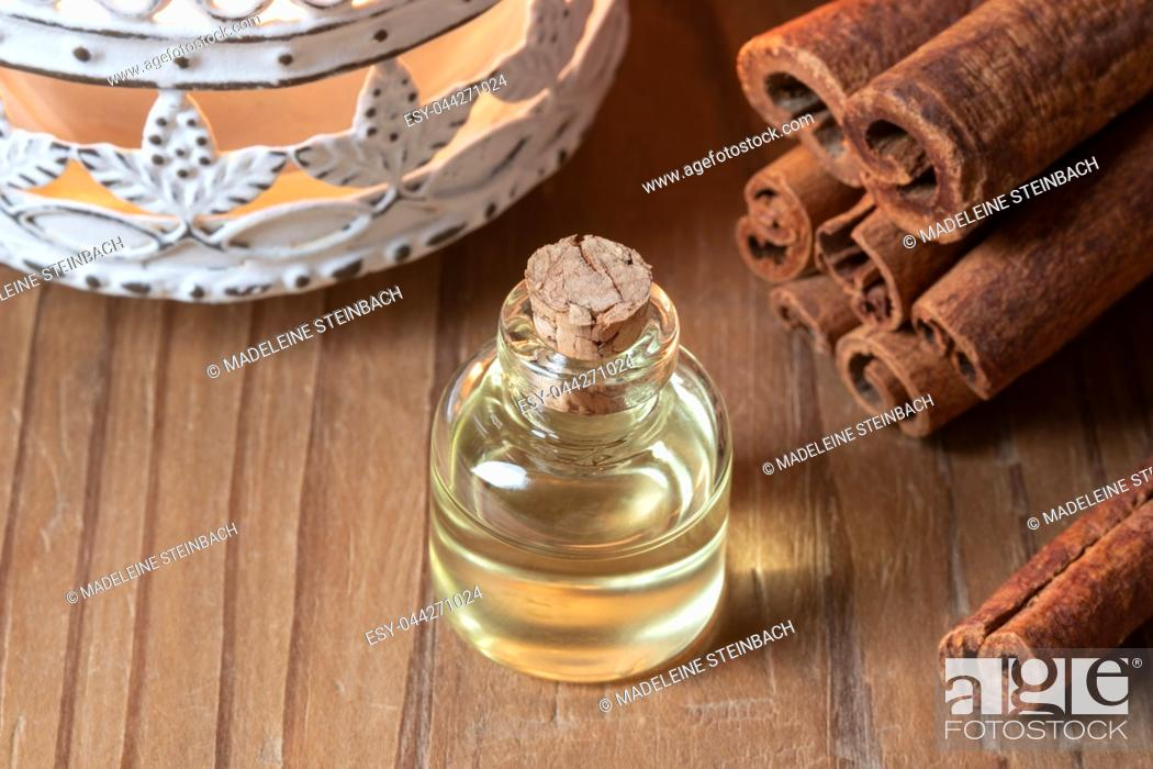 Stock Photo: A bottle of essential oil with cinnamon sticks.