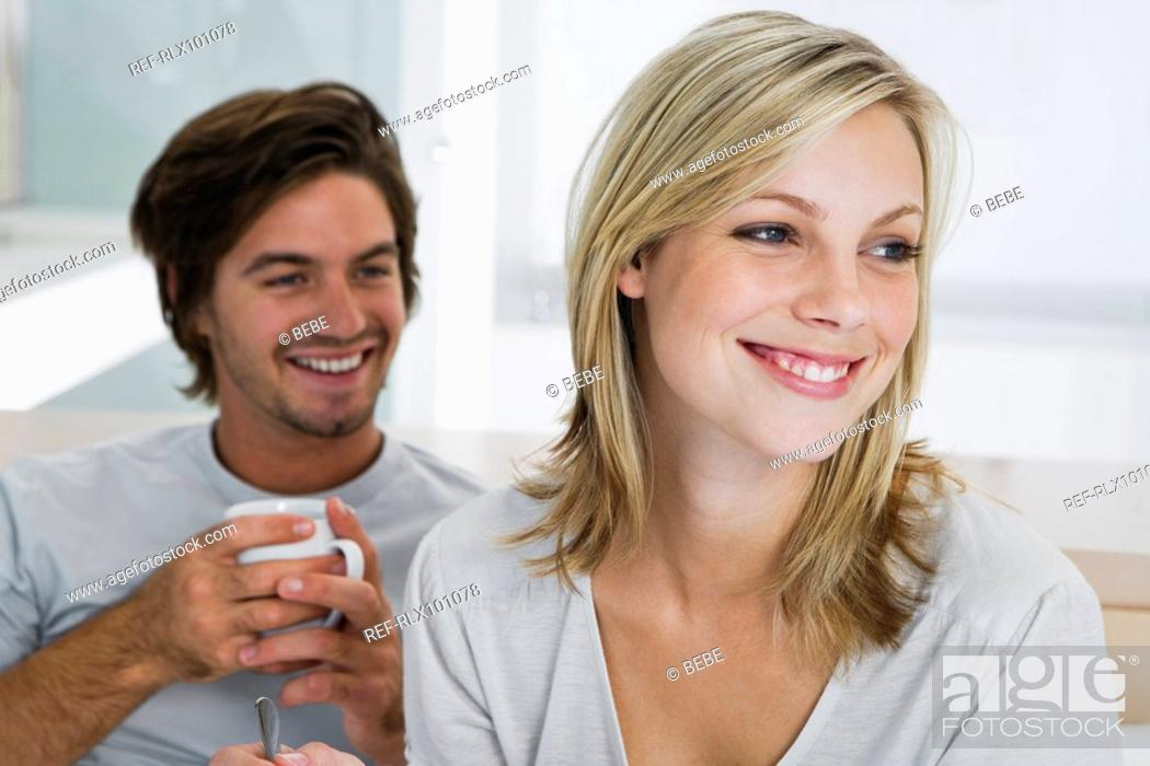 Stock Photo: Young couple sitting on bed, smiling, drinking coffee.
