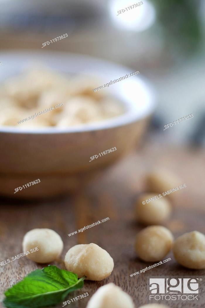 Stock Photo: Macadamia nuts in and in front of a wooden bowl.