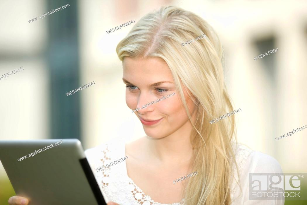Stock Photo: Germany, North Rhine Westphalia, Cologne, Young student with digital tablet, smiling.