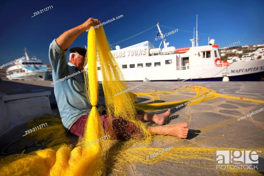 Stock Photo: Elderly greek fisherman repairing fishnets at the old harbour, Mykonos, Cyclades Islands, Greek Islands, Greece, Europe.