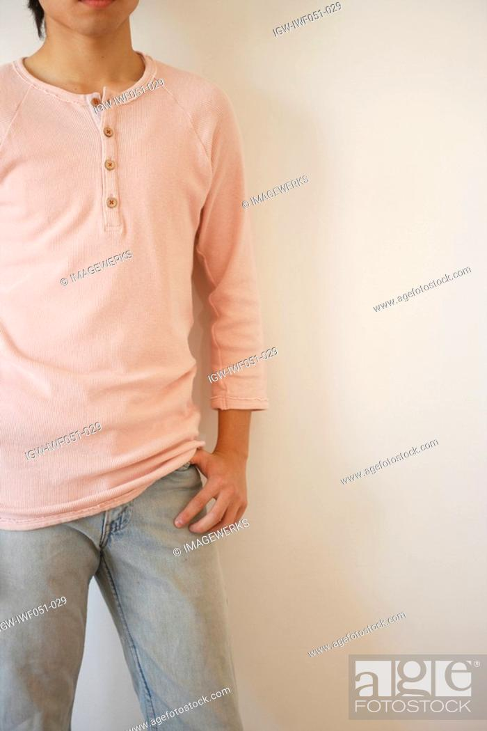 Stock Photo: Young man standing by wall.