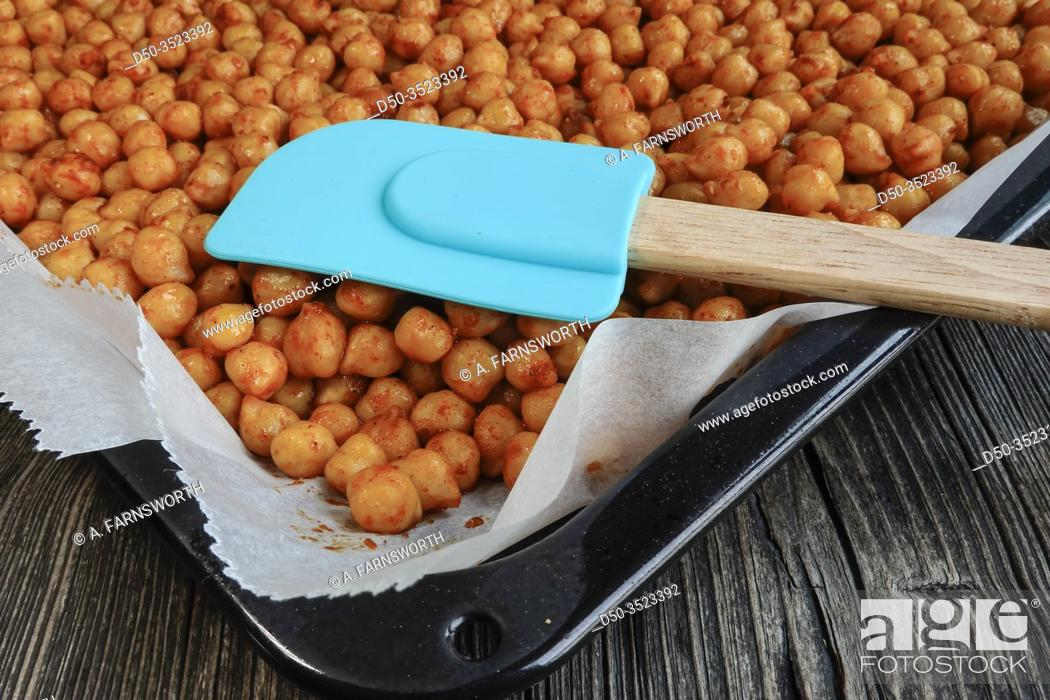 Imagen: Marinated and cooked chickpeas with spices on an oven tray.