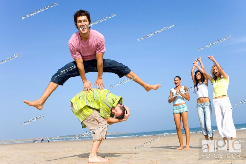 Stock Photo: Young man leaping over friend at beach, women cheering.