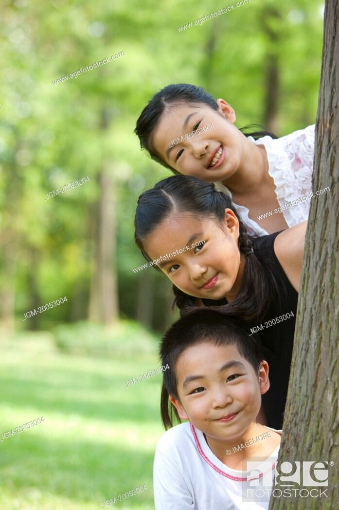 Stock Photo: Three children hiding behind a tree and looking at the camera with smile.