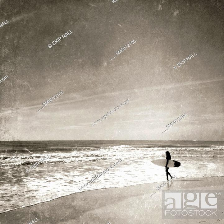 Stock Photo: Surfer on the beach about to go surfing and looking at the waves.