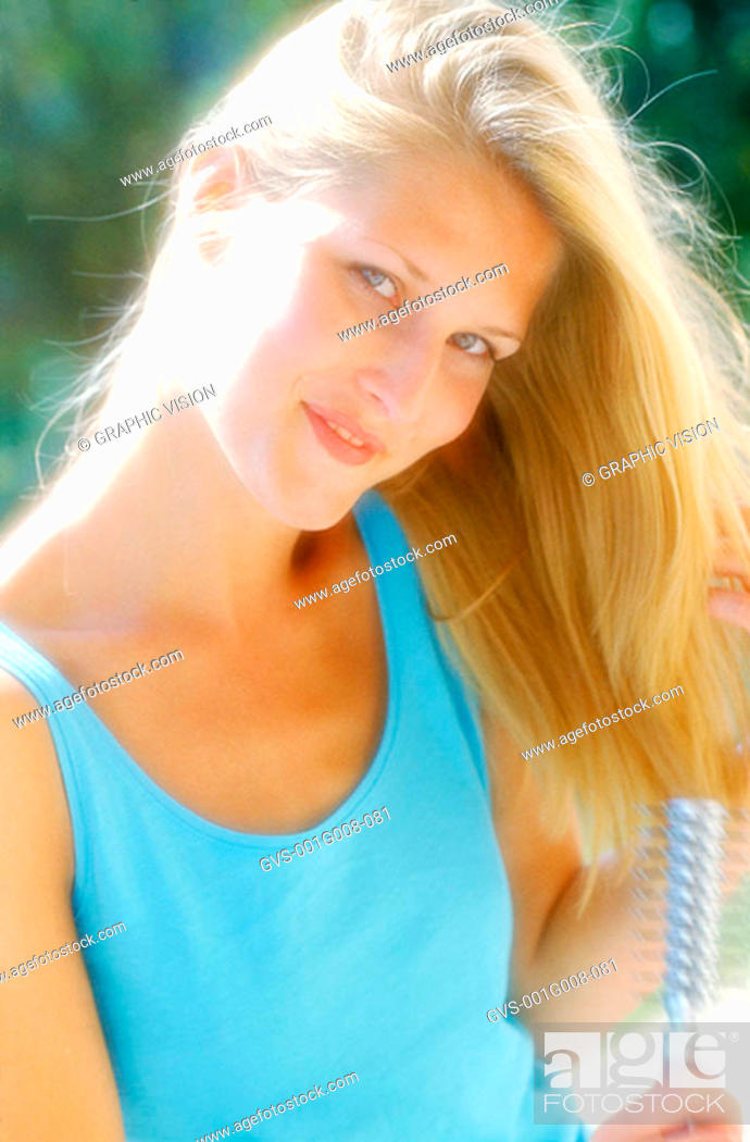 Stock Photo: Young woman brushing hair with a hairbrush.