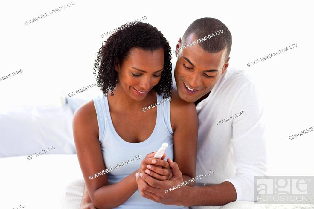 Stock Photo: Happy couple finding out results of a pregnancy test in the bedroom.