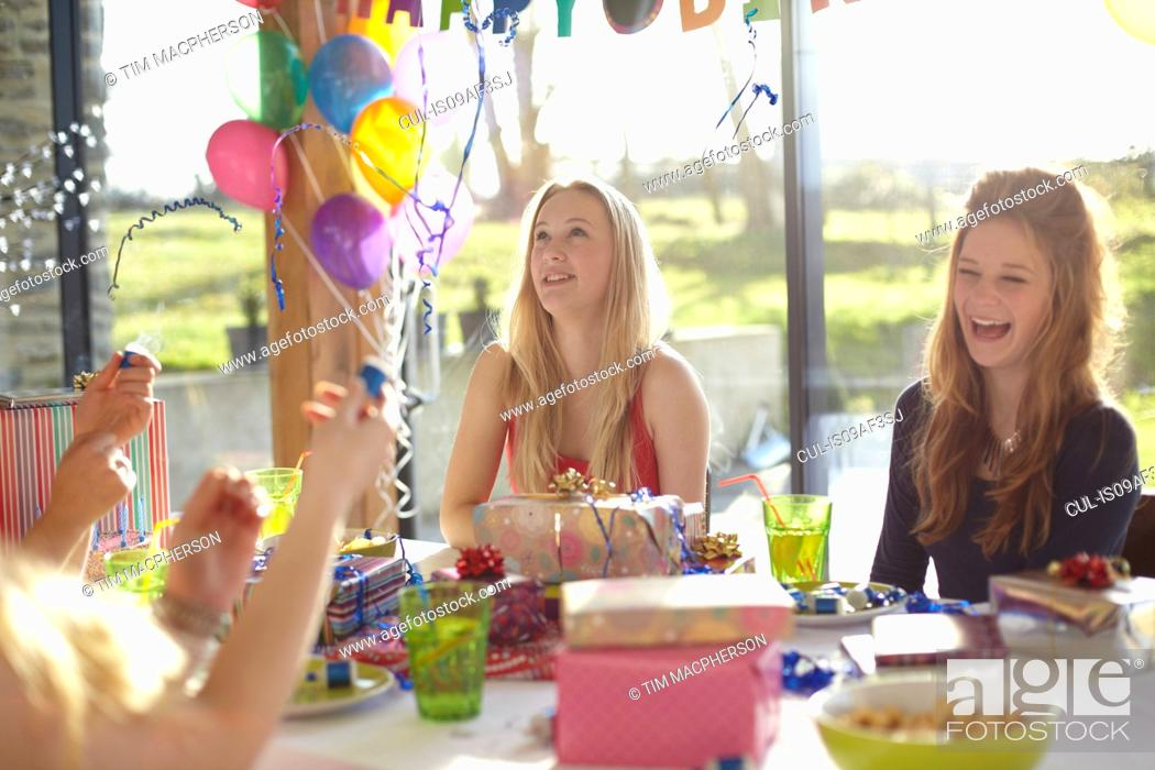 Stock Photo: Four teenage girls celebrating with bubbles at birthday party.