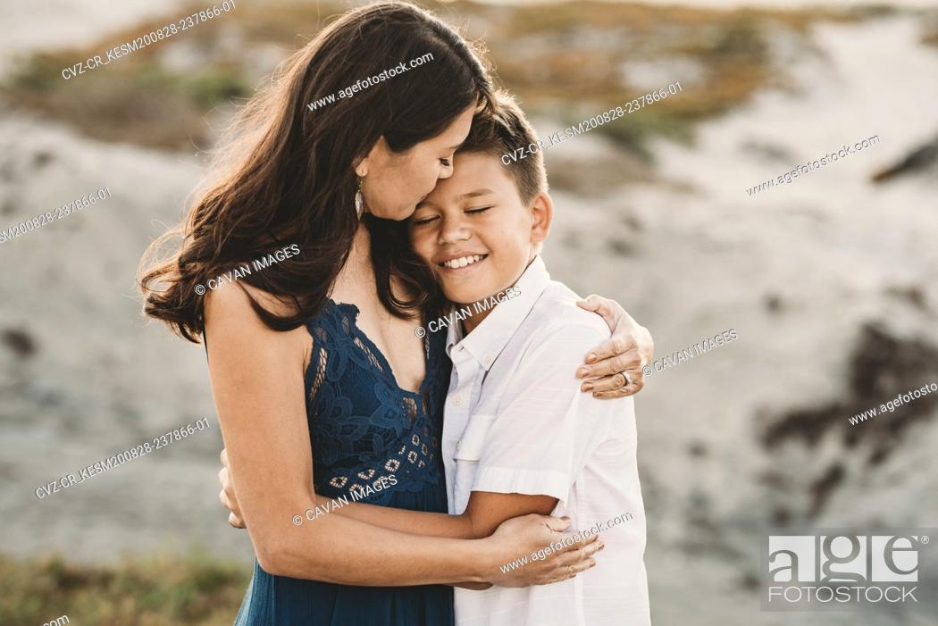 Stock Photo: Loving mother embraces smiling preteen son.