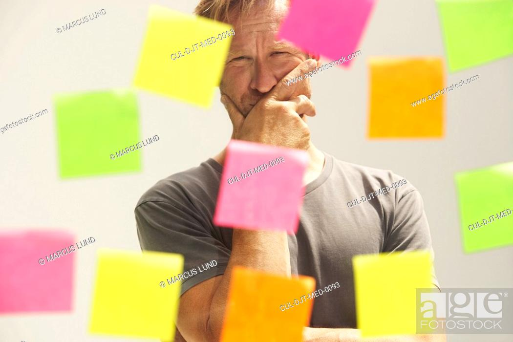 Stock Photo: Man looking at a window with colored PostIt Notes.