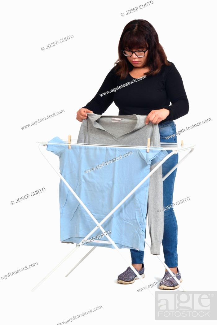 Stock Photo: front view of a latin woman hanging clothes on white background.