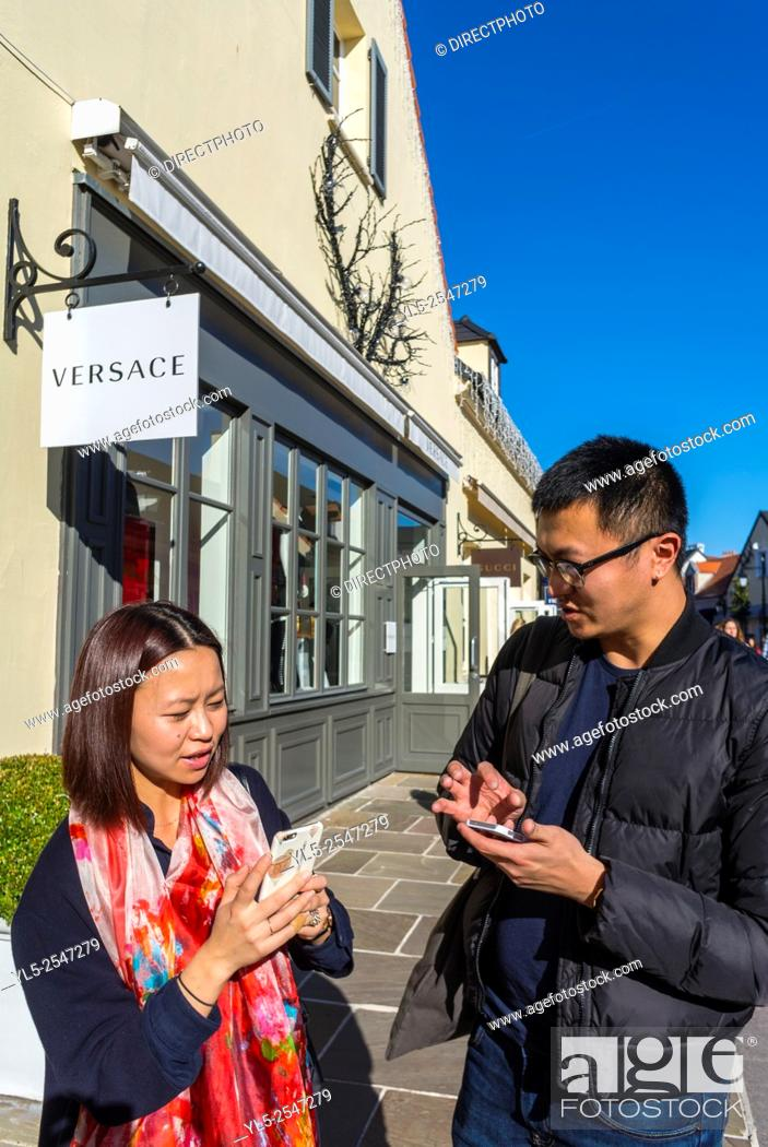 Stock Photo: Paris, France, Chinese Couple Tourists Shopping in Luxury Stores in La Vallee Village, Discount Shops, using Iphone on Street M.R.