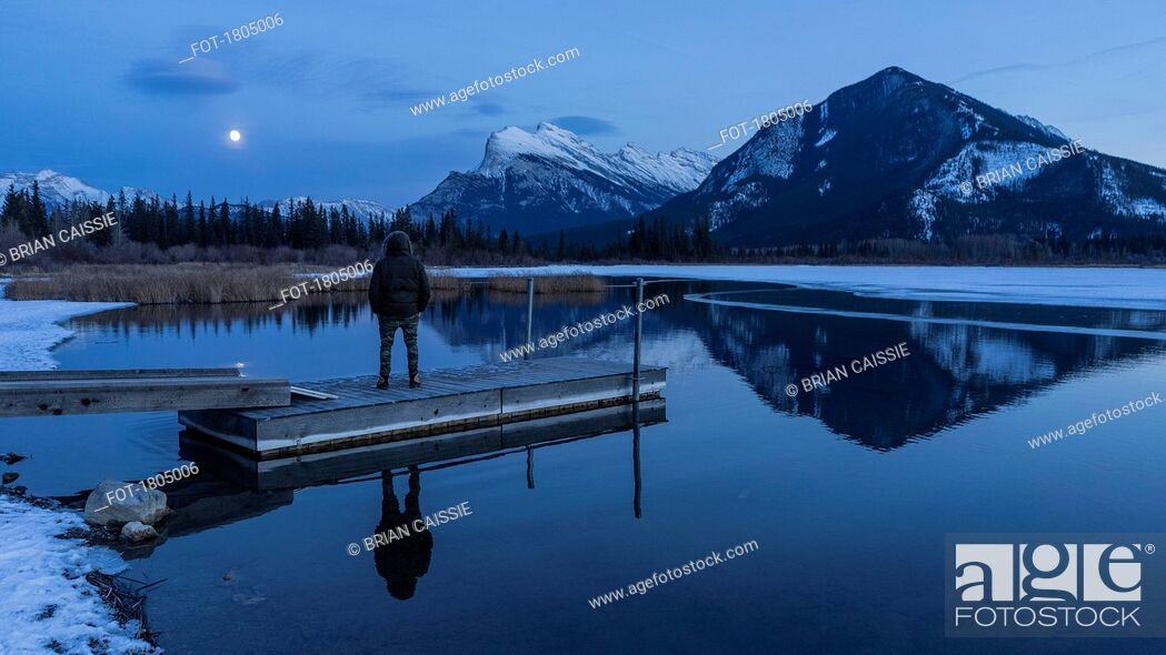 Stock Photo: Woman on tranquil winter lake dock, looking at full moon above mountains, Banff, Alberta, Canada.