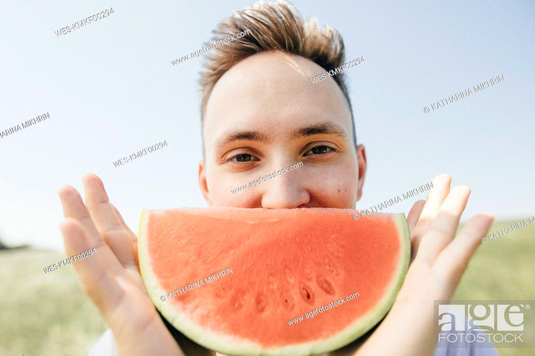 Stock Photo: Portrait of a young man holding a watermelon outdoors.