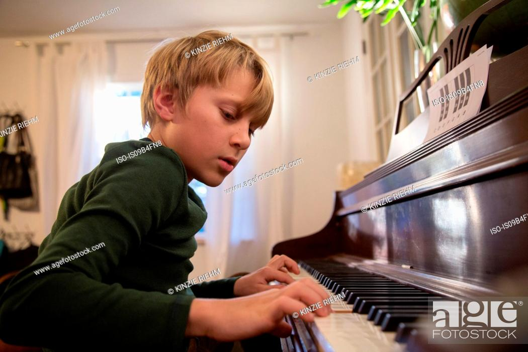 Stock Photo: Boy playing piano in living room.