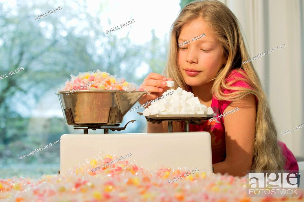 Stock Photo: Girl behind scales, weighing sugar cubes and a lot of candies.
