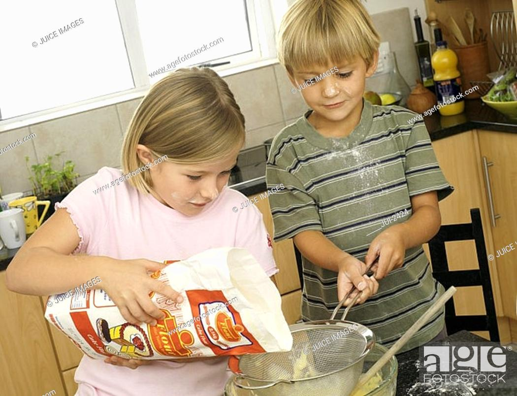 Stock Photo: Boy 5-7 and girl 6-8 making cake mix in kitchen, girl pouring flour into glass bowl tilt.