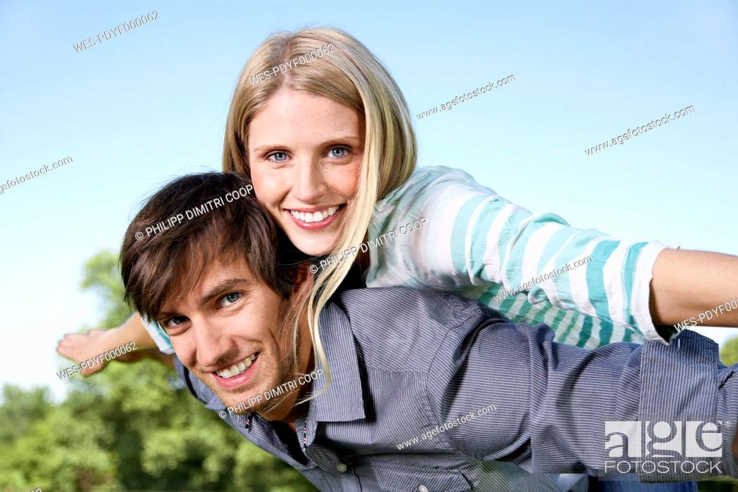 Stock Photo: Germany, Cologne, Young couple flying, smiling, portrait.