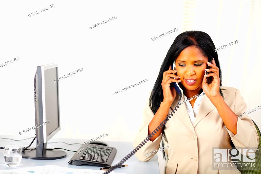 Stock Photo: Portrait of a young secretary talking on phone with two persons at the same time.