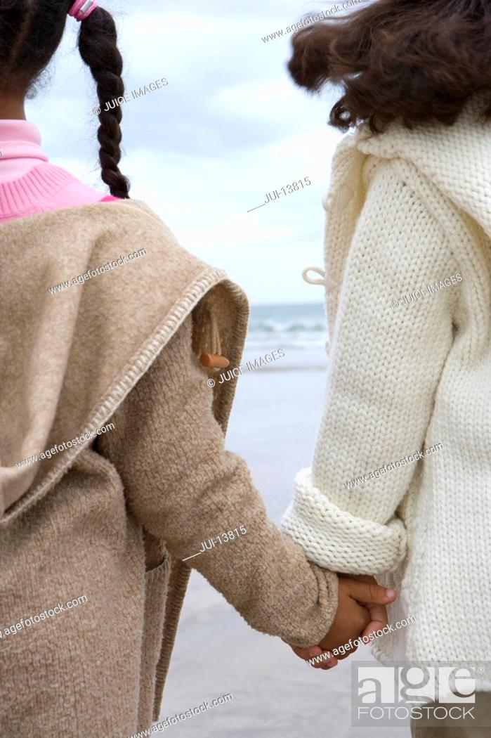 Stock Photo: Sisters 5-9 holding hands on beach, rear view.