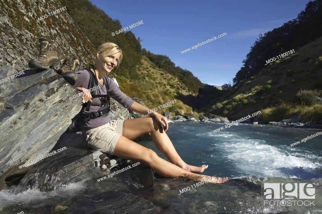 Stock Photo: Woman dipping her feet in river in forest valley.