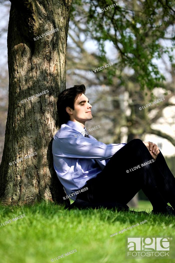 Stock Photo: A businessman leaning against a tree, resting.