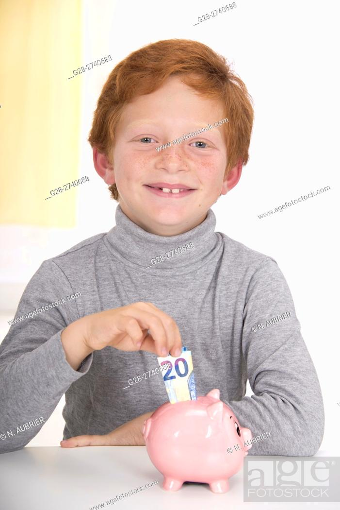 Stock Photo: Little boy with red hair, happy putting a 20 euros banknote into the slot of his pink piggy bank.