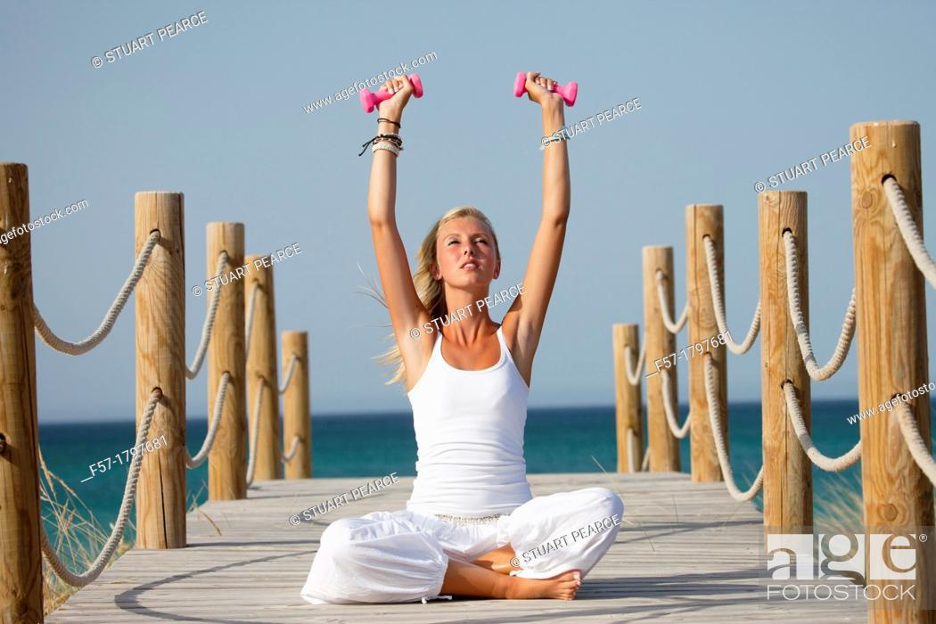 Stock Photo: Healthy young woman exercising on a boardwalk.