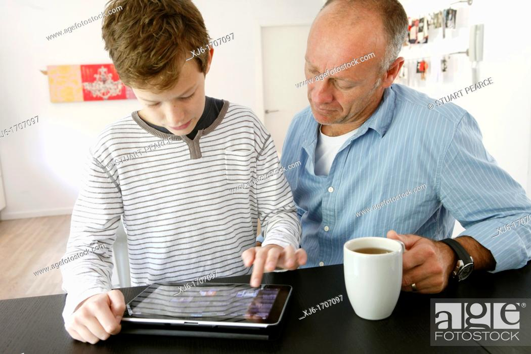 Stock Photo: Father and son using tablet computer.