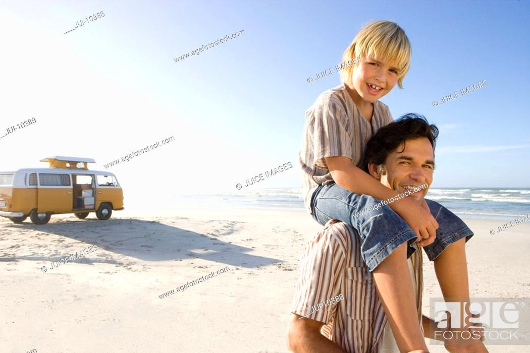 Stock Photo: Boy 6-8 on father's shoulders on beach, smiling, portrait.