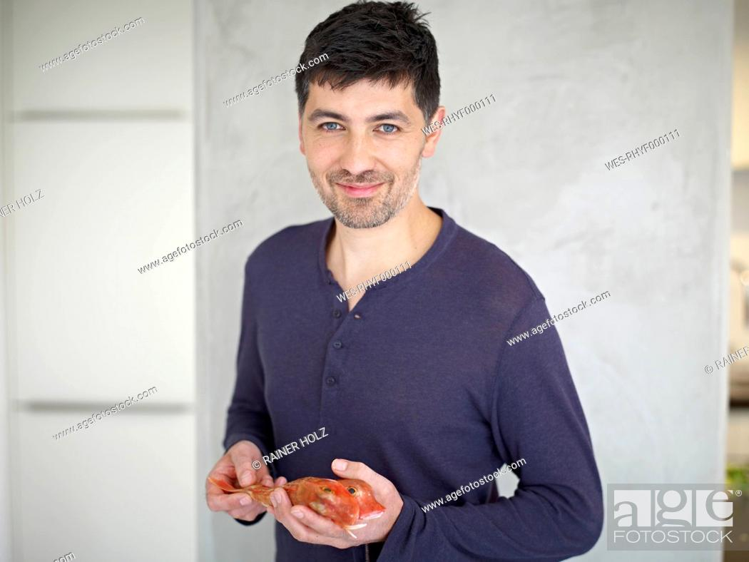 Stock Photo: Germany, Cologne, Mid adult man holding fish, portrait.
