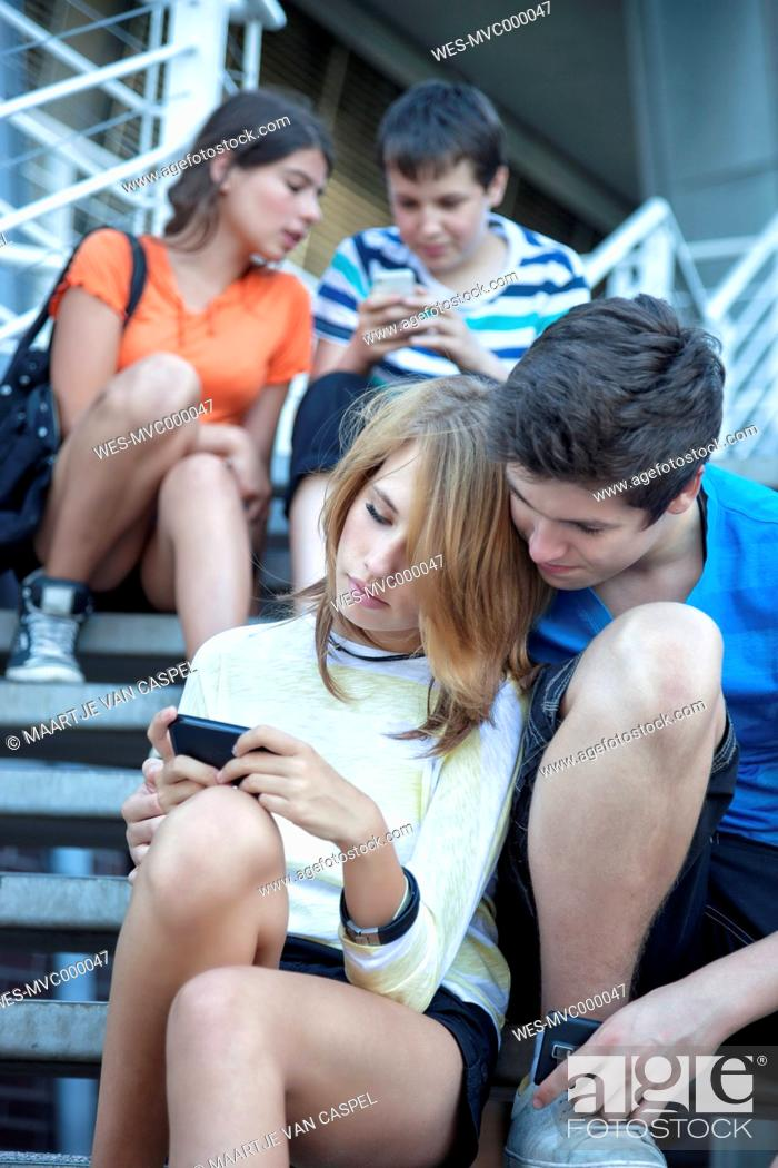 Stock Photo: Teenage friends using mobile devices on stairs.