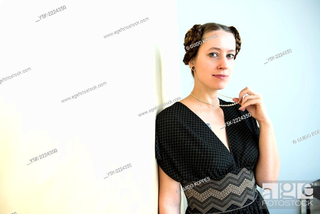 Stock Photo: Eindhoven, Netherlands. Young, attractive woman with tresses and tails in her hear, wearing a pearl neckless inherited from her grandmother.