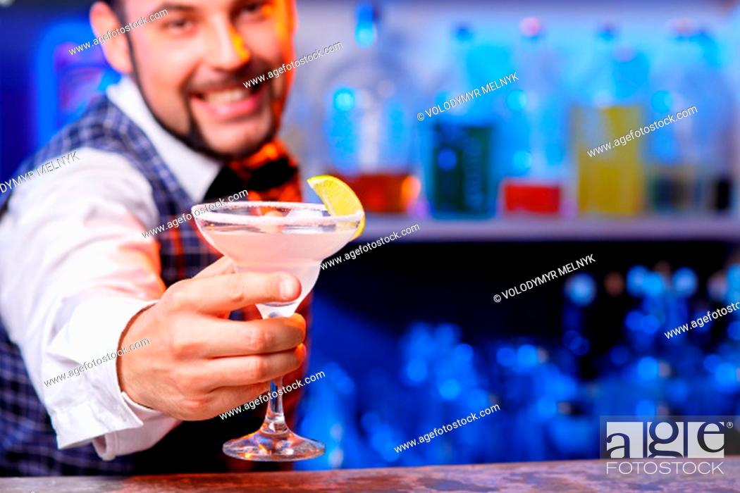 Stock Photo: The smiling barman at work, he preparing cocktails. Concept about service and beverages.