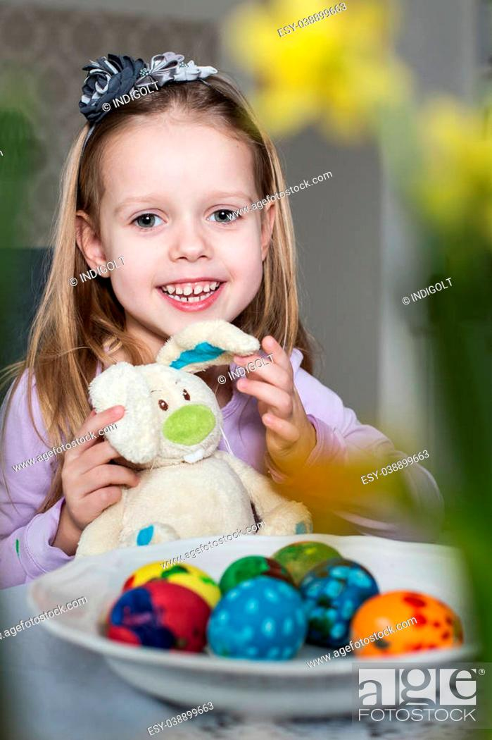 Stock Photo: Happy little girl with toy bunny and easter eggs. Easter, holiday and child concept.