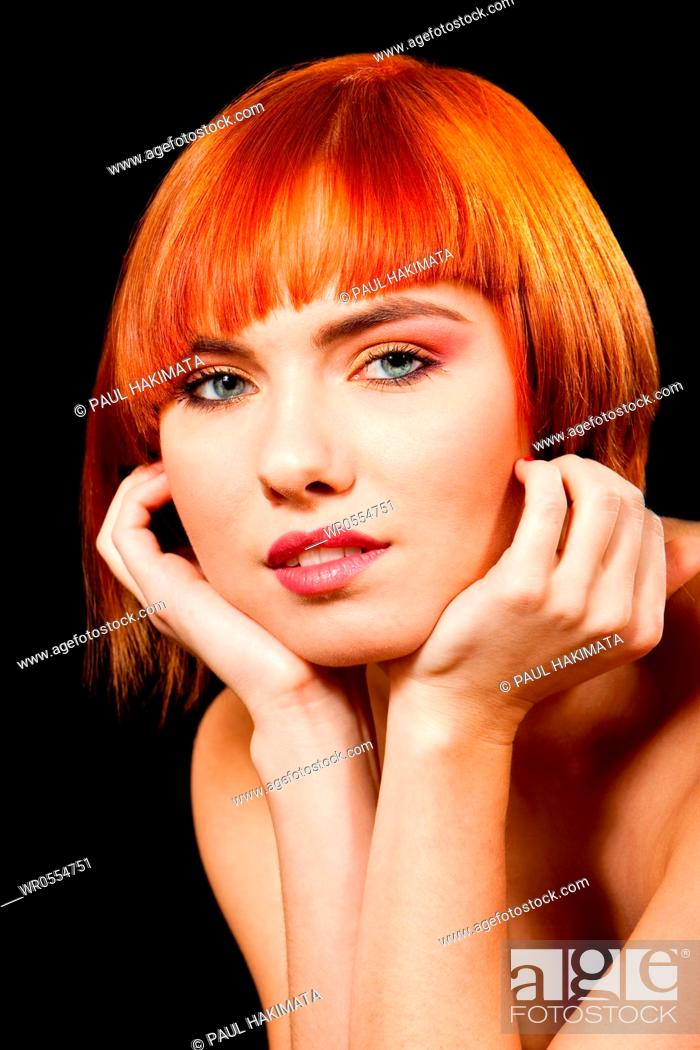 Imagen: Face of a beautiful Caucasian redhead girl with glossy blue eyes supporting her head with hands, isolated.