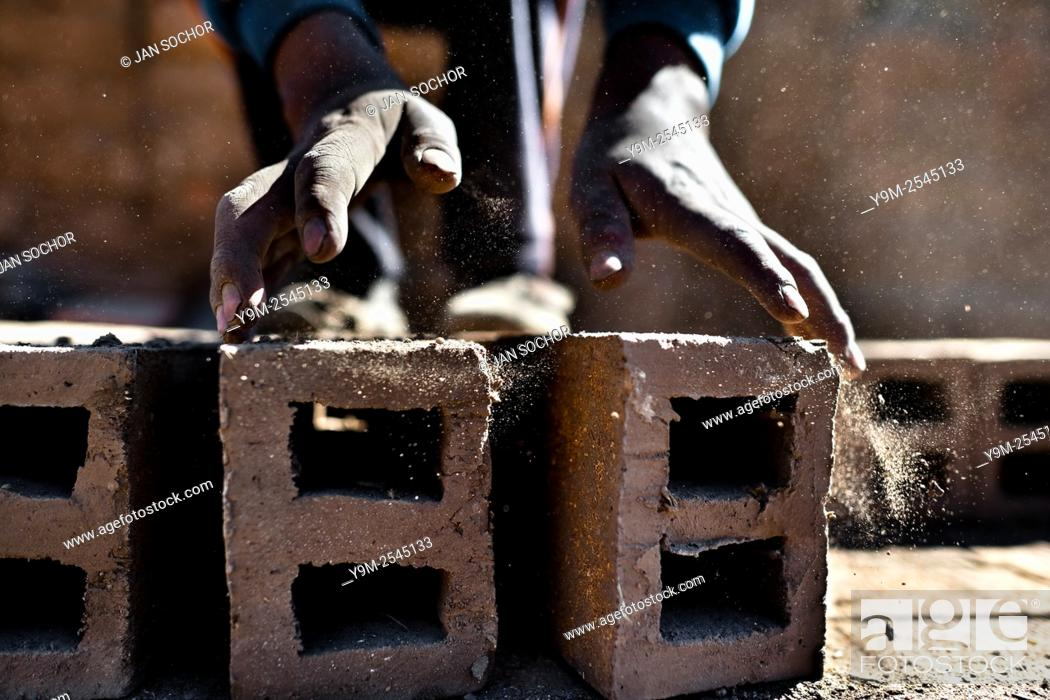 Stock Photo: A Peruvian boy turns raw bricks for drying at a brick factory in the outskirts of Puno, Peru, 2 August 2012. Child labour is a common practice at the artisanal.