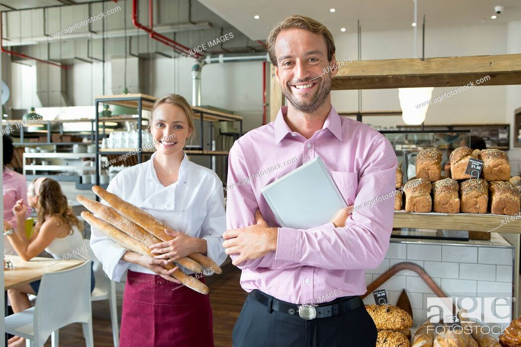 Stock Photo: Smiling baker with business owner holding bread in bakery.