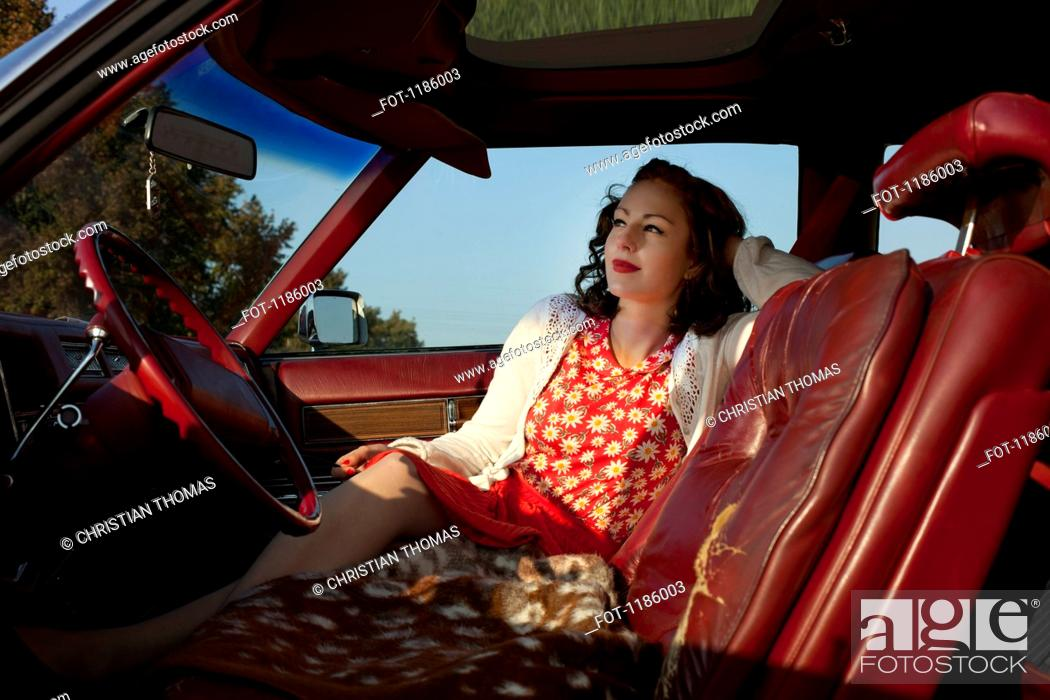Stock Photo: A pretty rockabilly woman sitting in the front seat of a vintage car.