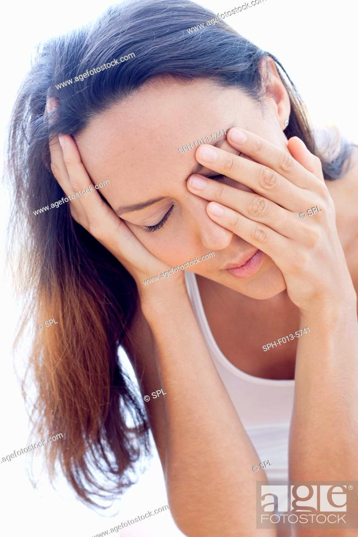 Stock Photo: MODEL RELEASED. Tired young woman rubbing her eyes.