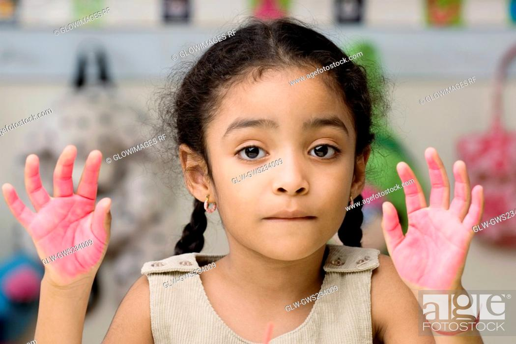 Stock Photo: Portrait of a girl showing paint covered hands.
