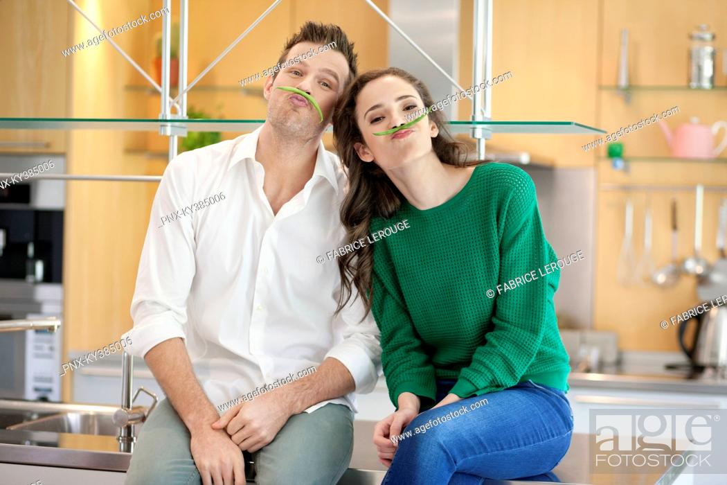Stock Photo: Couple playing with green bean in the kitchen.