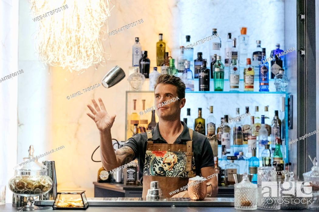 Stock Photo: Bartender mixing cocktail in a bar, using cocktail mixer.