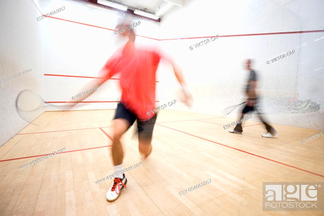 Stock Photo: Squash players in action on a squash court (motion blurred image; color toned image).