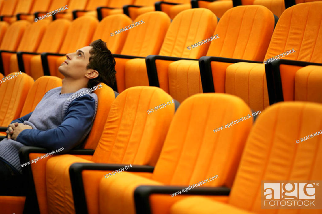 Stock Photo: Young man alone in lecture theatre.