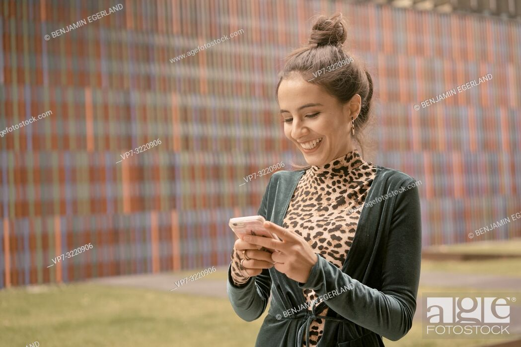 Stock Photo: laughing woman using smartphone.