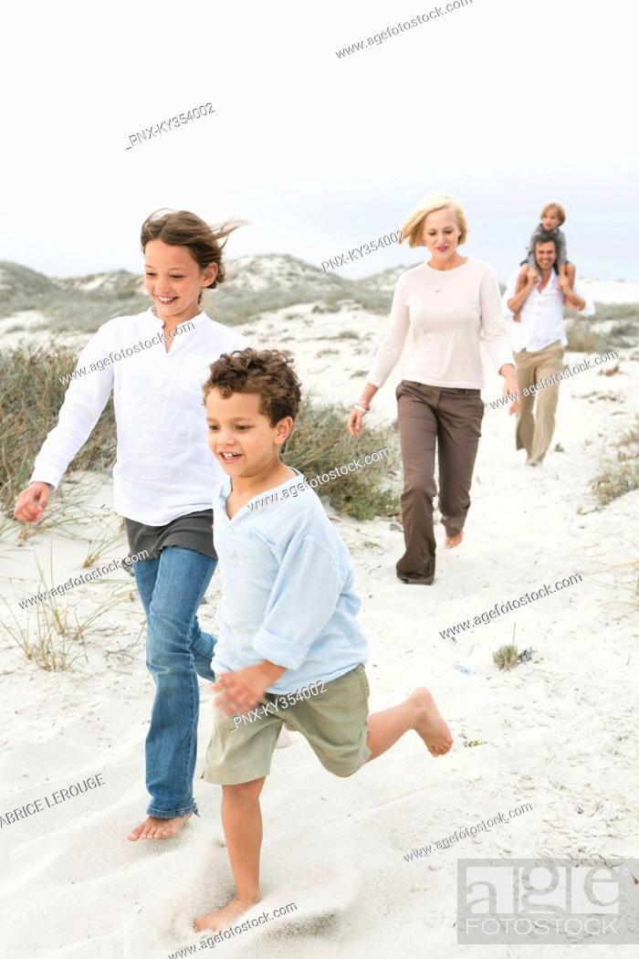 Stock Photo: Couple walking on the beach with their children.