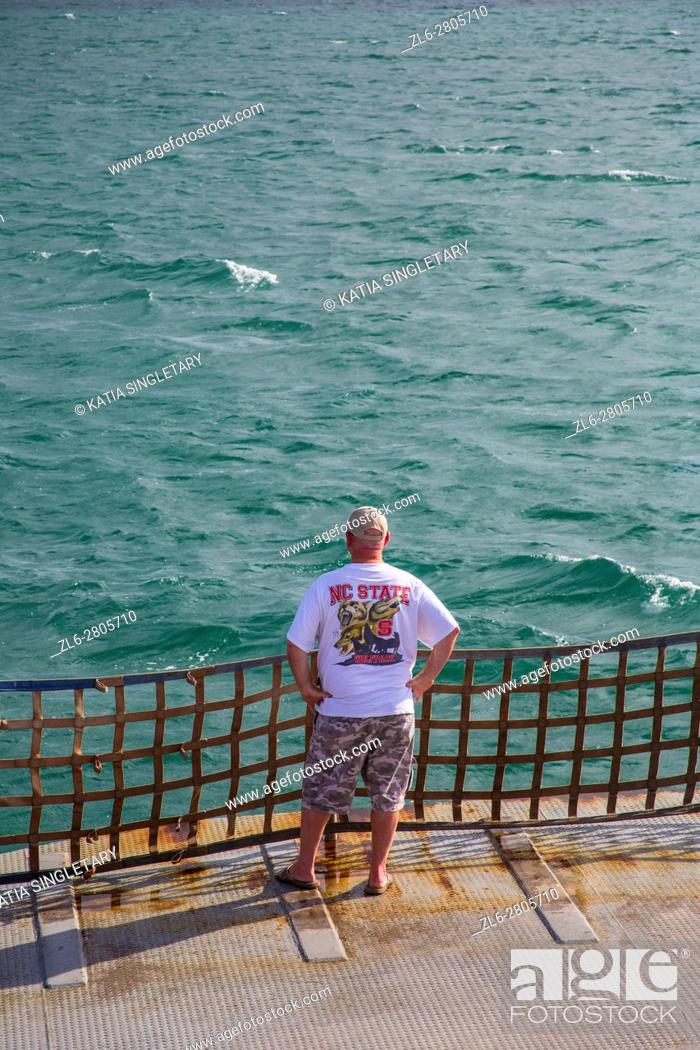 Stock Photo: Caucasian American man with a NC State teeshirt, short and a baseball cap looking at the ocean during the crossing on the Ferry in the outer banks of North.